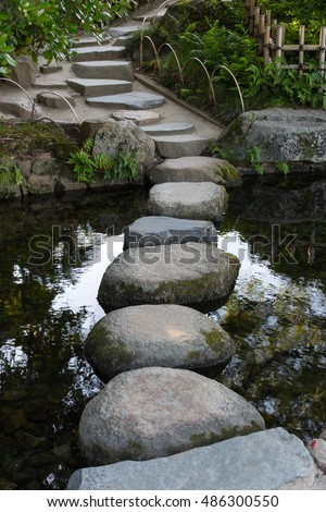 Zen stone path in a Japanese Garden across a tranquil pond in Okayama