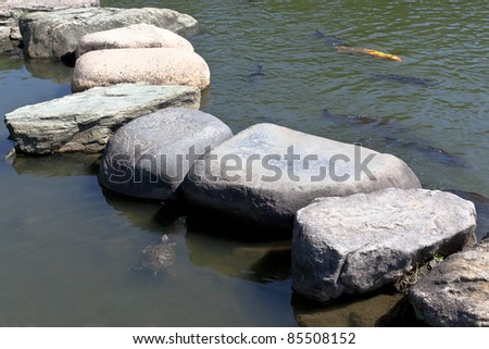Zen stone path in a Japanese Garden across a tranquil pond with carps and turtles - stock photo