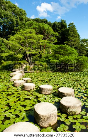 Zen stone path in a Japanese Garden near Heian Shrine.Stones are surrounded by lotus leaves - stock photo