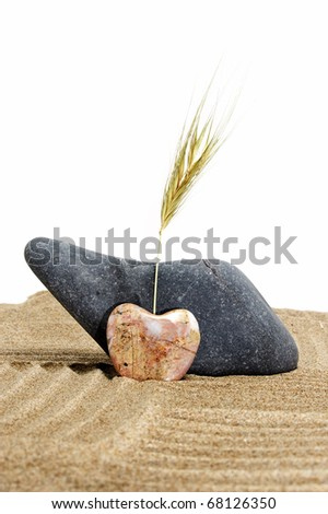 zen stones, one heart shapped, on a zen garden in a white background - stock photo