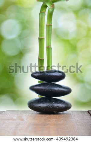Zen stones with green bamboo on wooden table with green blur bokeh background
