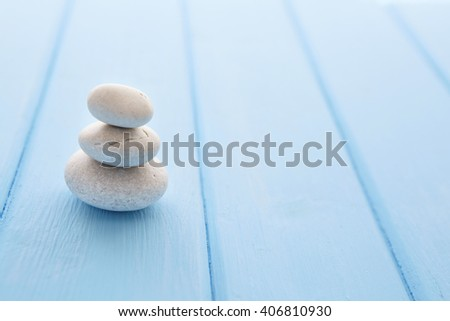 Zen stones wooden table. Pile planar stones on the old blue wooden rustic table. - stock photo