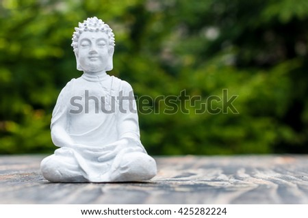 Zen, yoga and meditation concept. White Buddha on green relax background - stock photo