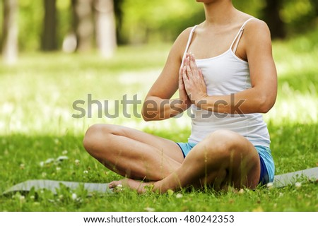 Zen yoga position woman on the grass.