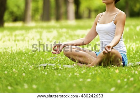 Zen yoga woman lotos position on the grass.