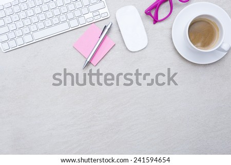 zenithal view of a business desk consisting on a a cup of coffee with a coffee saucer, wireless mouse, a keyboard, a pink eyeglasses and a pink post-it with a pen - suitable for copy space - stock photo