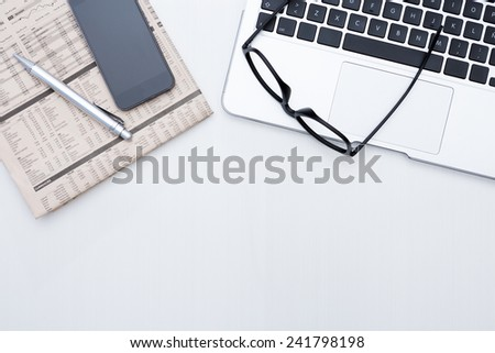 zenithal view of a business desk consisting on a laptop, a financial newspaper and a pen, a mobile phone and a black eyeglasses on a grey desk background - suitable for copy space - stock photo