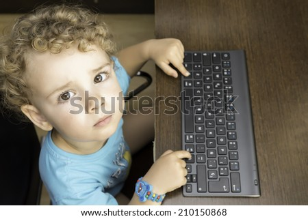 zenithal view of a portrait of a child using a wireless computer keyboard looking to the camera sitting on a desk - focus on the face - stock photo