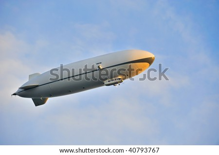 Zeppelin airship in the blue sky - stock photo