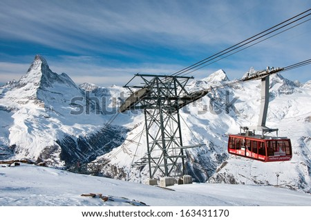 ZERMATT -?? JANUARY 18: Cable car climbing up from Blauherd to Rothorn with Matterhorn in the background on January 18, 2013 in Zermatt, Switzerland. The Rothorn paradise is one of the main ski areas. - stock photo