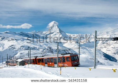 ZERMATT -?? JANUARY 17: Red train climbing up to Gornergrat station on January 17, 2013 in Zermatt, Switzerland. The Gornergrat rack railway is the highest open-air railway in Europe. - stock photo