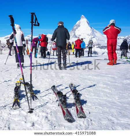 ZERMATT, SWITZERLAND -APRIL 14, 2016: Skiers prepare to ski at  Gornergrat train station with Matterhorn peak in background, a summit station above Zermatt in Switzerland. - stock photo