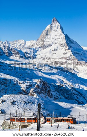 Zermatt, Switzerland - December 31, 2014-The train of Gonergratbahn running to the Gornergrat station in the famous touristic place with clear view to  Matterhorn. The starting point of the ski slope. - stock photo