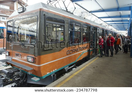 ZERMATT, SWITZERLAND - MARCH 04, 2009: Unidentified skiers embark Gornergrat train at Zermatt station. Zermatt is one of the most popular ski resorts in Switzerland. - stock photo