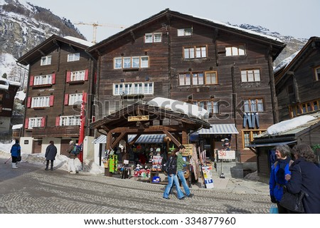 ZERMATT, SWITZERLAND - MARCH 04, 2009: Unidentified tourists walk by the street in Zermatt, Switzerland. Zermatt is one of the most popular ski resorts in Switzerland. - stock photo