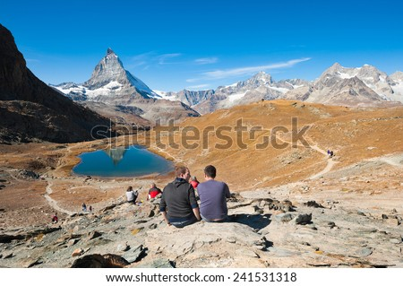 ZERMATT, SWITZERLAND- SEPT 29, 2009: Tourists on hiking path with a view of the Matterhorn peak in the background.  - stock photo