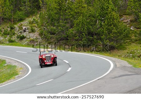 ZERNEZ, SWITZERLAND - JUNE 15: A red MG TC takes part to the Summer Marathon classic car race on June 15, 2014 near Zernez. This car was built in 1948 - stock photo