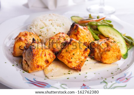 Zesty chicken shish kebabs served with rice pilaf on a tiny lavash bread garnished with cooked vegetables zucchini, green beans and carrots - stock photo