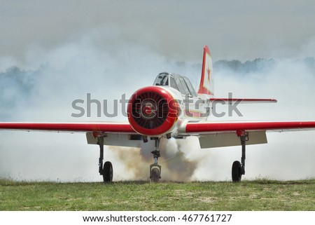 Zhitomir, Ukraine - May 26, 2012: Light trainer and aerobatic plane Yak-52 producing heavy smoke on the airfield after landing