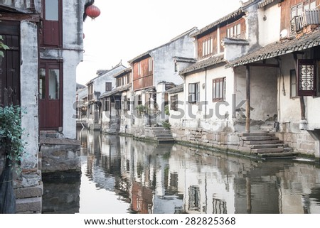 Zhouzhuang, a Shanghai tourist attraction. Old houses and bridge reflection in a village canal. - stock photo