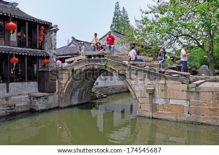 ZHOUZHUANG, SHANGHAI-MAY 5: tourists relaxing over on old bridge. Zhouzhuang water village is Shanghai tourist attraction with 1000000 visitors year May 5, 2008 Zhouzhuang, China