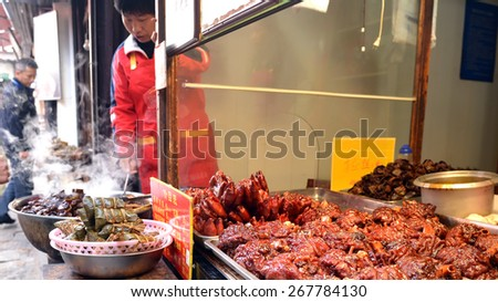 ZHUJIAJIAO, CHINA - NOVEMBER 10, 2014: Pig feet, ham hocks and other food for sale at a small shop in the ancient water town of Zhujiajiao located in the Qingpu District of Shanghai. - stock photo