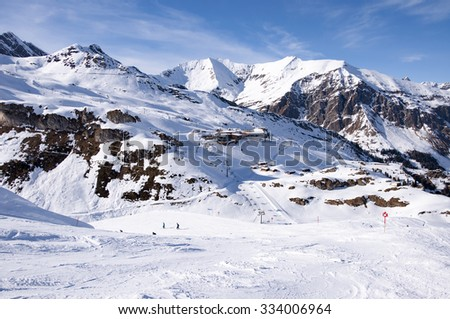 Zillertal Alps at Hintertux Glacier with a cable car station, ski lifts and pistes in sunset light - stock photo