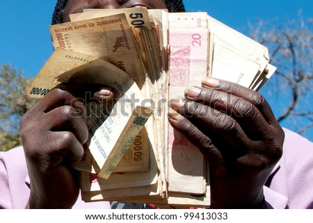 zimbabwe money being held and handled