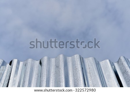 Zinc fence with sky for background - stock photo