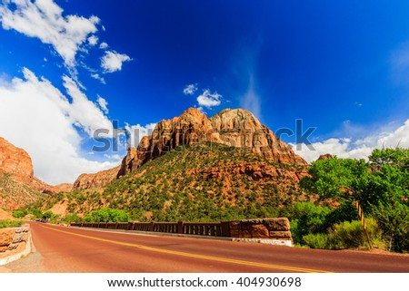 Zion National Park, USA. Excellent with red asphalt scenic road among the picturesque mountains of orange and red sandstone. - stock photo