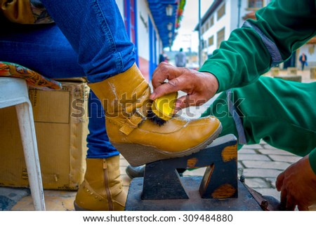 ZIPAQUIRA, COLOMBIA - FEBRUARY 3, 2015: Closeup of shoeshiner working on yellow boots in the center, historic Zipaquira city, located middle Colombia, 48 km from Bogota.
