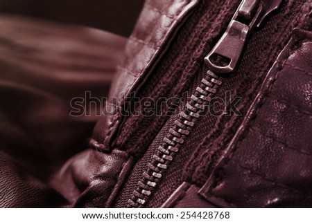 Zipper detail on an elegant brown leather jacket. Close up photo, nice light effect.