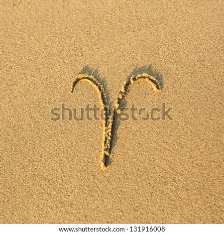 Zodiac sign Aries, drawn on the facture beach sand. (zodiac signs series) - stock photo