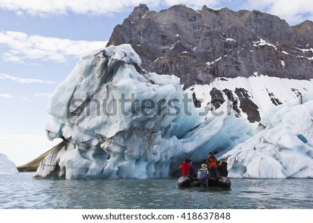 zodiac with people in front of an iceberg - stock photo