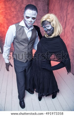 Zombie couple with freaky make up for Halloween or All Souls Day. Painted faces.