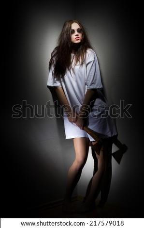 Zombie girl with axe on grey wall - stock photo