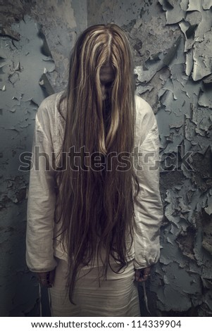 zombie girl with long hair in an abandoned building - stock photo