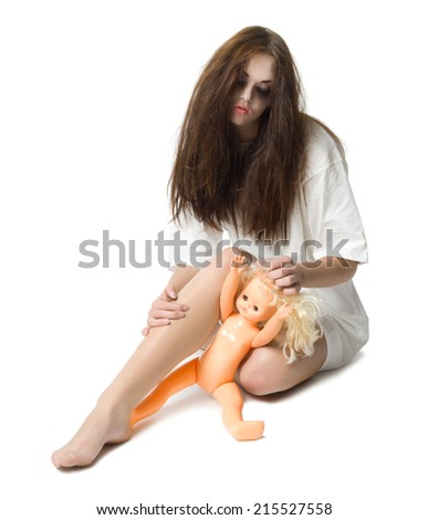 Zombie girl with plastic doll isolated on white - stock photo