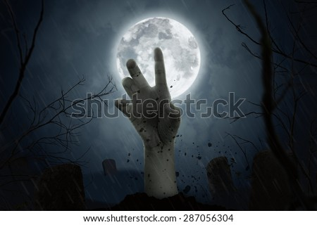 zombie hand coming out of his grave in full moon night. - stock photo