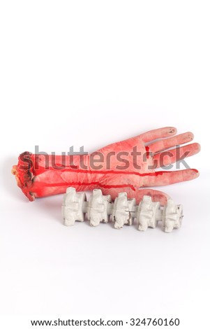 Zombie hand with human spine isolated on white - stock photo