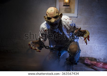 zombie, Man chained with blood and knife, has a severed leg blood - stock photo