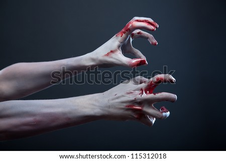 Zombie stretching bloody hands, Halloween theme - stock photo