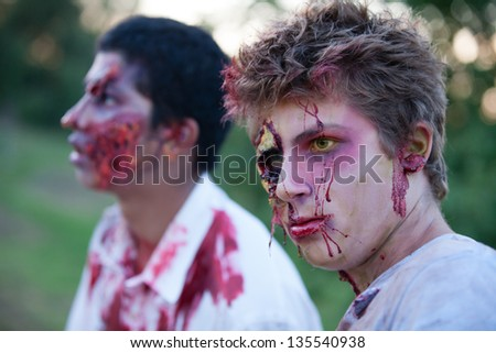 Zombie teens outside with yellow eyes looking at camera - stock photo