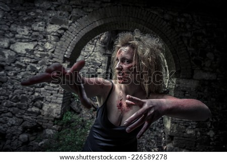 Zombie woman in an abandoned house trying to catch her victim - stock photo