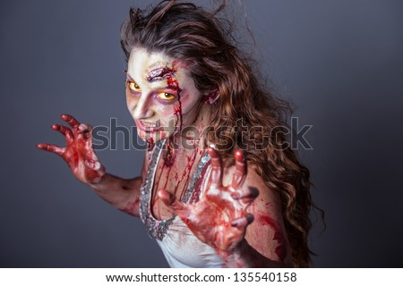 Zombie woman  with yellow eyes looking at camera - stock photo