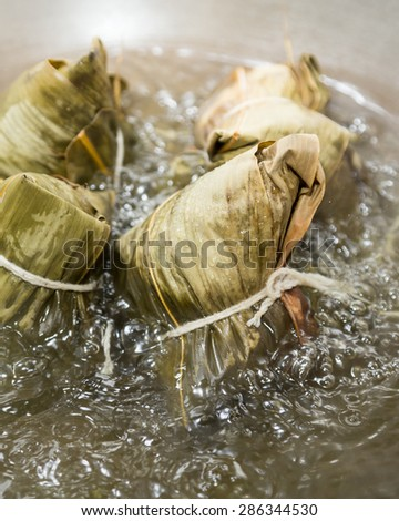 Zongzi boiling in a wok. Zhongzi is a traditional Chinese food eaten during Dragon boat Festival - stock photo