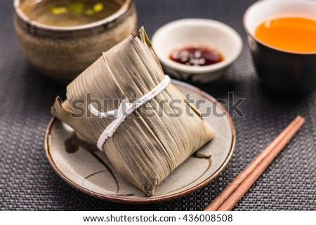 Zongzi or Asian Chinese sticky rice dumplings with Yellow tea, soup, sauce and chopsticks on dark table surface. Zongzi is a traditional Chinese food eaten during the dragon boat festival. - stock photo