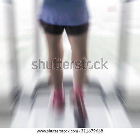 Zoom burst radial blur of unknown woman running with treadmil  fitness.woman fitness.female  - stock photo