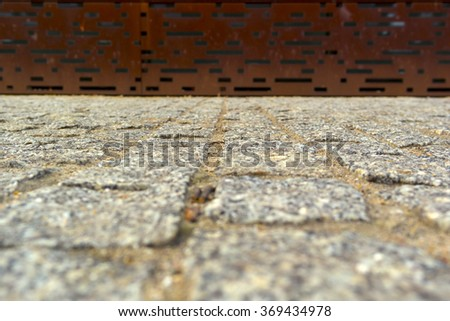 Zoom effect granite pavement with a rusty metal wall.