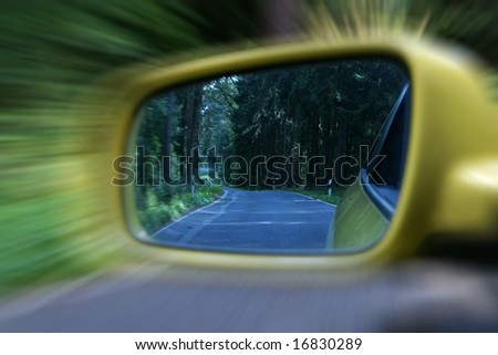 Zoom effect on exterior rear view mirror with rural woodlands - stock photo